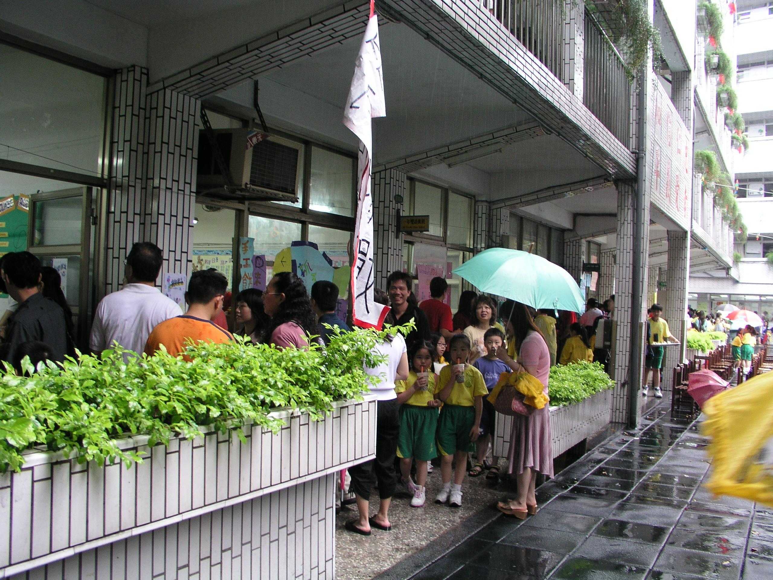 因為下大雨,學生與家長們都必須擠在走廊上